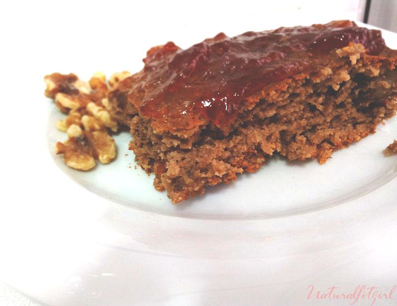 brownie con mermelada de fresa y nueces sobre fondo blanco