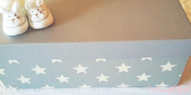 patucos bebe sobre caja gris de estrellas blancas
