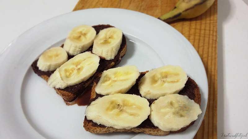 tostada integral con chocolate desgrasado y plátano sobre plato blanco