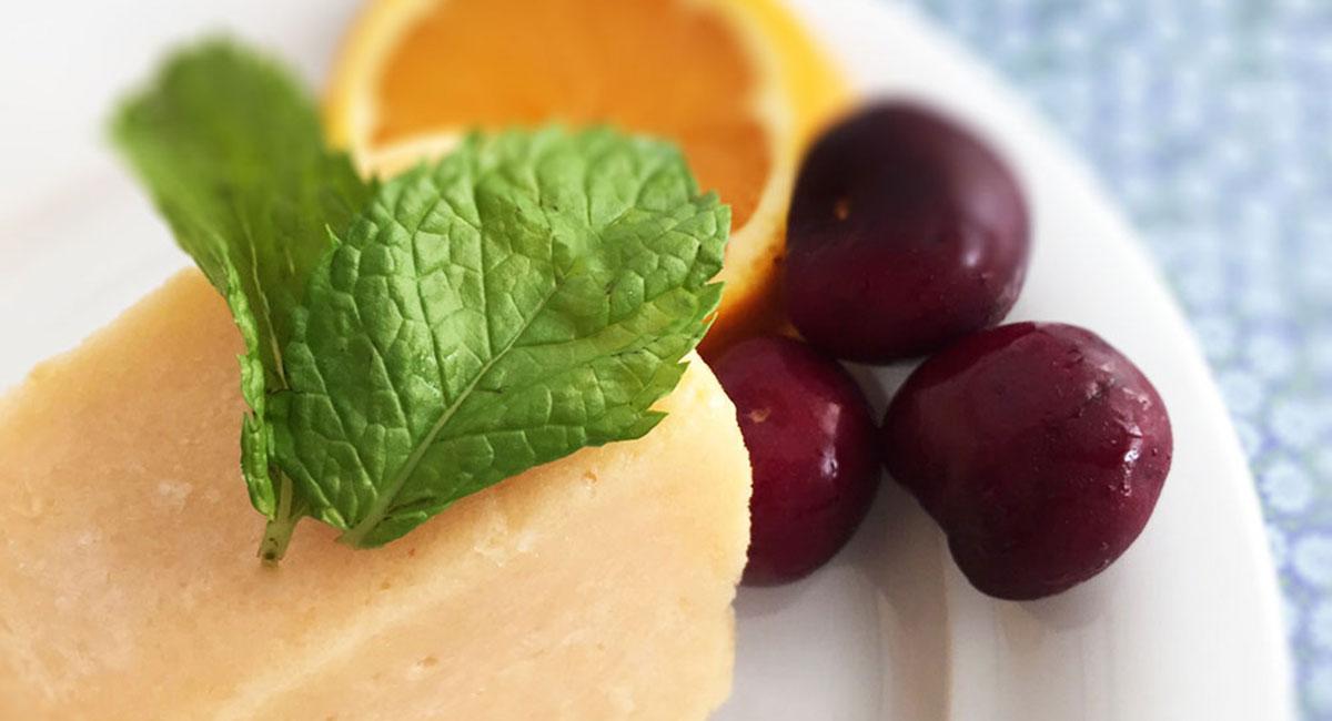 helado de melocotón decorado con menta y acompañado de frutas