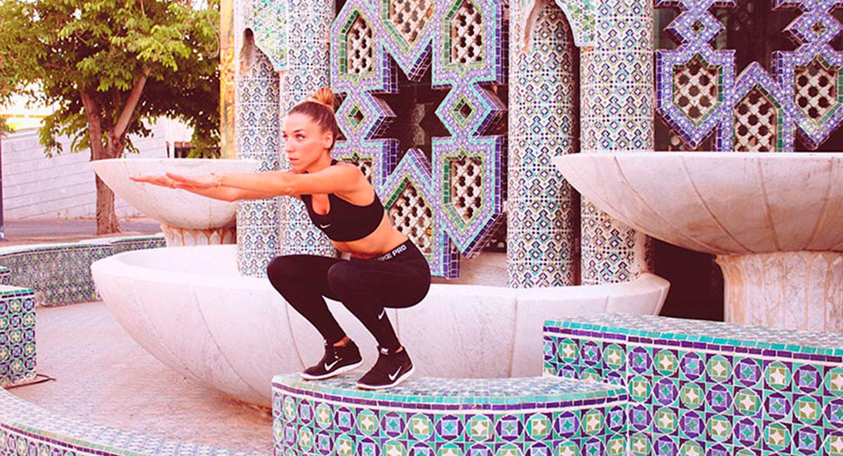 chica haciendo sentadillas en edificio mosaicos