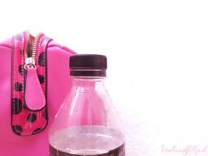 bolso rosa y botella de agua sobre fondo blanco