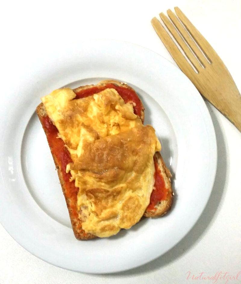 tostada de tortilla francesa y tomate frito casero en plato blanco